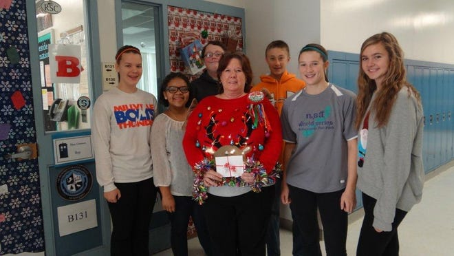 Teacher Robin Roche won Lakeside Middle School's ugly sweater contest. She's pictured with some members of the National Junior Honor Society, which judged the event.