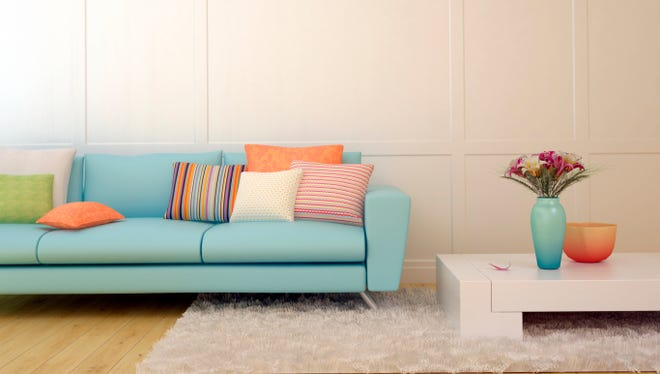 Blue sofa with colorful pillows and a white coffee table.