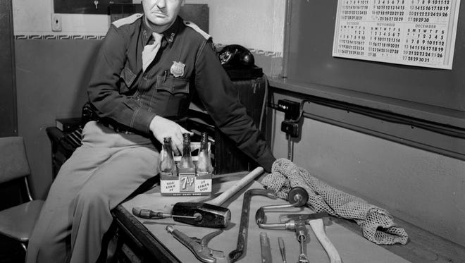 Officer Orville Beers with burglar's tools, 1954