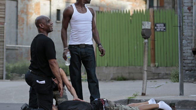 June 22, 2015: Ohio State Senator Cecil Thomas, left, and bystanders call out for help as they to tend to a shooting victim as he lay near the intersection of Race and Elder Streets, across from Findlay Market, where has was shot during a three-person shootout about 7:00 p.m. in the Over-the-Rhine neighborhood of Cincinnati, on Monday, June 22, 2015. The victim was transported to University of Cincinnati Medical Center where he died of his injuries. Thomas was in the neighborhood as he was taking part in peace march through the neighborhood just moments before the gunfire.
