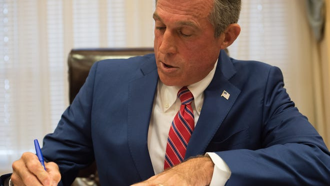 Gov. John Carney signs an executive order for budget smoothing on Saturday, June 30, 2018.