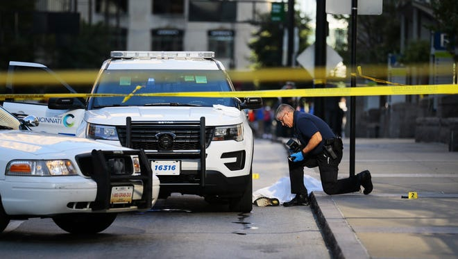 Police investigate the scene of an officer-involved shooting that left a man suspected of robbery dead. Police said the man pulled a knife on officers after being tracked from the Vine Street Kroger location to East Fifth and Main streets Sunday morning.