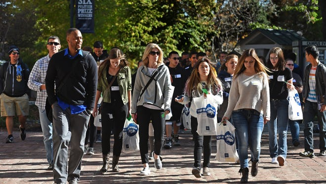 Andre Lawson, front left, a recruitment coordinator at UNR, leads a group of high school students visiting the university.