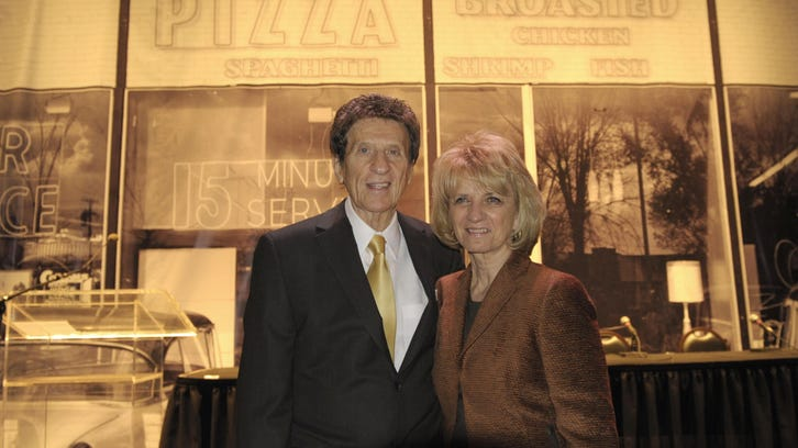 Mike and Marian Ilitch celebrate the 50th anniversary of Little Caesars, which began in 1959 with their Garden City, seen behind them. The company has grown into thenation'sthird-largest pizza chain, behind Pizza Hut and Domino's.