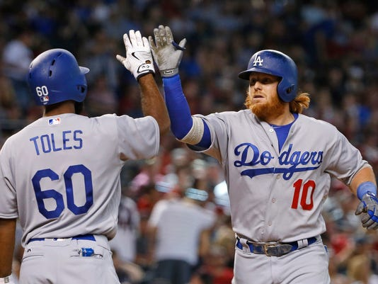 Los Angeles Dodgers' Justin Turner (10) celebrates his two-run home run against the Arizona Diamondbacks with Andrew Toles (60) during the eighth inning of a baseball game Sunday, July 17, 2016, in Phoenix. (AP Photo/Ross D. Franklin)