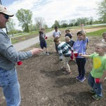 Tom McInnis, Assistant Director of Winnebago County Parks Department, discusses with a Valley Christian second grade group of students what their efforts will achieve by planting a monarch seed mixtures at Winnebago County Park on Monday, May 16, 2016.