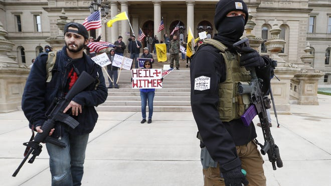 Protesters carry rifles near the steps of the Michigan State Capitol building in Lansing, Mich., on April 15. Flag-waving, honking protesters drove past the Michigan Capitol to show their displeasure with Gov. Gretchen Whitmer's orders to keep people at home and businesses locked during the new coronavirus COVID-19 outbreak.