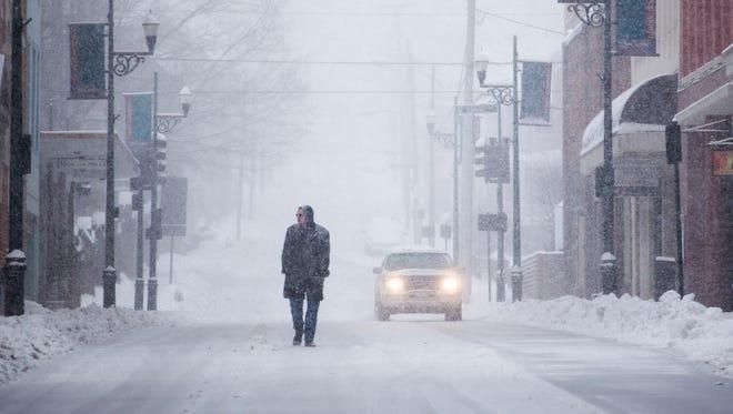 Glenn Schudel walks down West Beverley Street as snow falls on downtown Staunton Thursday afternoon.