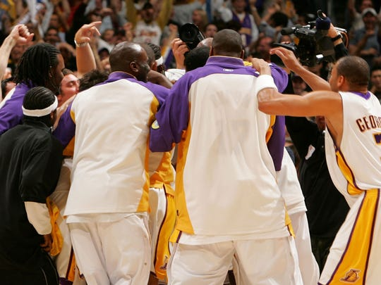 The Los Angeles Lakers swarm Kobe Bryant after he hit