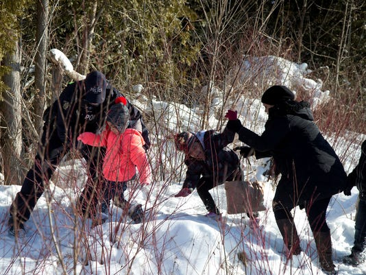 Royal Canadian Mounted Police (RCMP) officers assist a family that claimed to be from Sudan as they walk across the U.S.-Canada border into Hemmingford, Canada, from Champlain in New York, U.S., February 17, 2017.