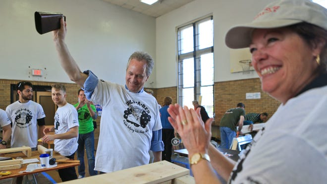 Mayor Greg Fischer rings a bell to signal a completed bed frame as Ellen Hesen, his chief of staff, smiles and claps during the Build A Bed program Saturday that's part of the Give a Day week of service events in Metro Louisville. Dozens of volunteers helped craft beds for kids in need.