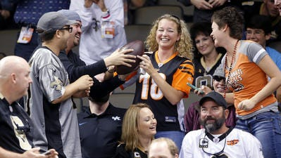 Bengals fan Christa Barrett happily accepts a football. Earlier in the game, tight end Jermaine Gresham tried to flip the ball to her after he scored a touchdown, but a Saints fan muscled in to grab the ball and refused to give it to her despite fans urging him to.
