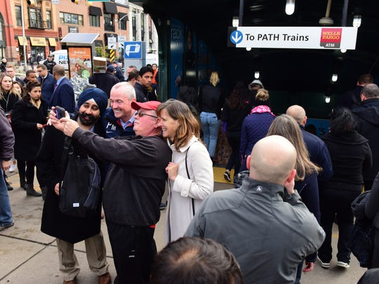 Center, Phil Murphy, New Jersey Governor Elect, takes a selfie shot with a commuters at the Hoboken Path Station Wednesday morning with current Hoboken Mayor Dawn Zimmer and Hoboken Mayor Elect Ravi Bhalla.