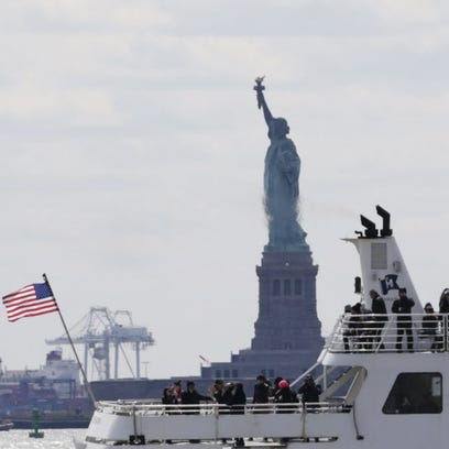 A tourist boat sails past the Statue of Liberty in