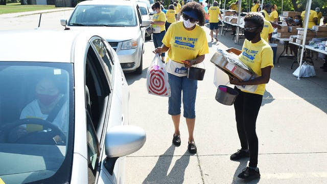 """Volunteers Alexis Holmes (right) and Anita Rollins distribute school supplies during a drive-thru """"Hope in Christ Back to School"""" event at Friendship Baptist Church Saturday in Ames. See more photos on page A3. Photo by Nirmalendu Majumdar/Ames Tribune"""