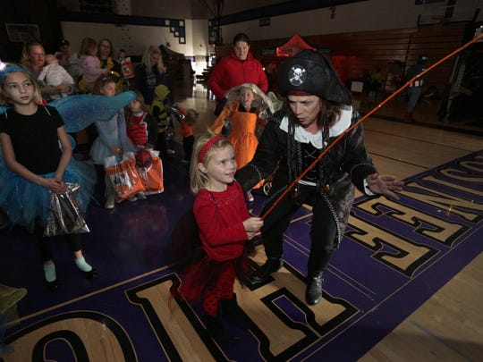 Susie Durst, right, of Mosinee helps Miley Wayerski, 5, of Junction City ?fish? at the Healthy Haunting Expo and Dance. At left is Megan Wayerski, 9, Miley?s sister.