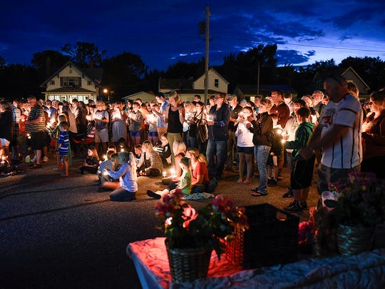 People gather for a candlelight vigil Tuesday to remember Alayna Ertl, 5, in the parking lot of St. Anthony Catholic Church in Watkins.