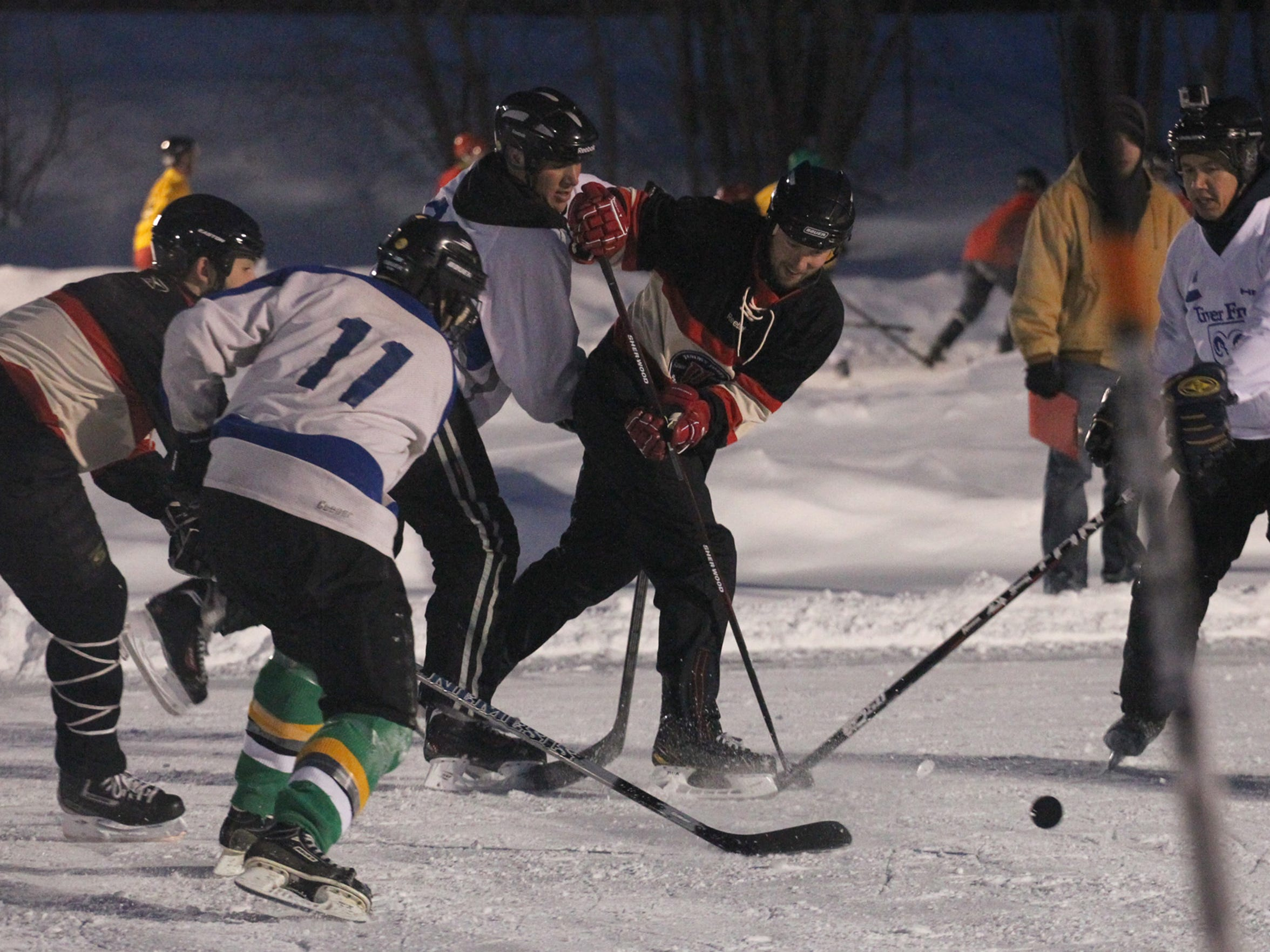 Players battle for the puck at the 2013 Midwest Freeze Leinenkugel's Classic Adult Pond Hockey tournament at Sunny Vale Park in Wausau.
