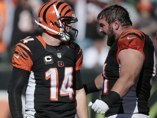 Bengals quarterback Andy Dalton (14) is met by center