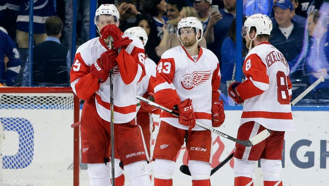 Detroit Red Wings players, from left, Danny DeKeyser, Darren Helm and Justin Abdelkader react to the team's 1-0 loss to the Tampa Bay Lightning during Game 5 Thursday, April 21, 2016, in Tampa.