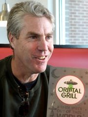 Owner Brett Hayes talks about the menu for Orbital Grill during an interview at the establishment in Waynesboro on Monday, Dec. 15, 2014.  Hayes also owns Zeus Theater located adjacent to the restaurant.