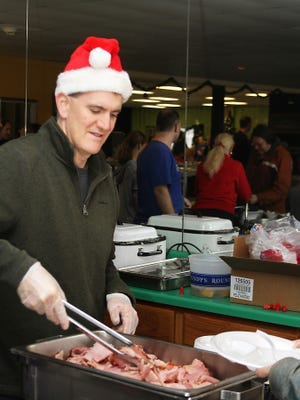 In this file photo, Mark Pollard serves up ham at the Christmas meal at Father Carr's Place 2B for those in need in keeping with Father Carr's mission to help those in need.