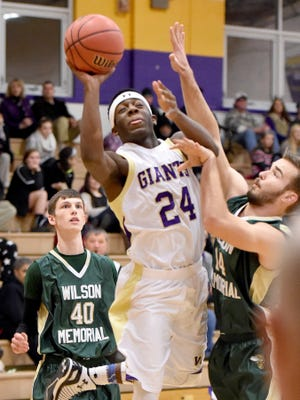 Waynesboro's DeVante Robinson takes the ball up and shoots while guarded by Wilson Memorial's John Leavell III and Mack Cullen during a basketball game played in Waynesboro on Wednesday, Jan. 7, 2015.