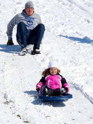 """Nalani Herron, 3, of Waynesboro grins with joy and holds on as her father, Frankie Herron watches. She rides the sled downhill at Ridgeview Park in Waynesboro on Tuesday, Feb. 17, 2015. """"I did it, Daddy! ... I did it!"""" she exclaims after riding the sled solo for the first time."""