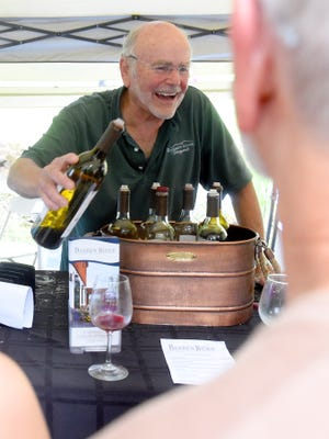 John Higgs of Barren Ridge Vineyards laughs as he pours wine.  He shares conversation with festival goers visiting the tent to sample the various wines from his winery.