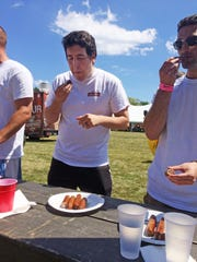 Sheboygan Press Media reporter Jason Smathers chews on a bratwurst during the Brat Eating Contest at Kiwanis Park in Sheboygan on Saturday.