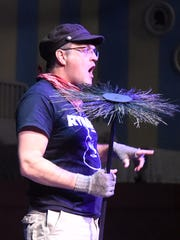 """Jeff Ryman holds a prop chimney sweep as he portrays """"Bert"""" during rehearsal on July 30, 2015."""