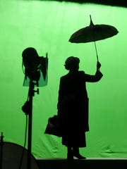 Liz Leone creates the iconic silhouette of Mary Poppins while filming against a green screen for a commercial on July 8, 2015.