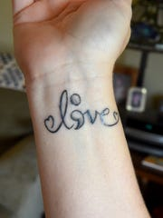 "Kim Sours has ""l ; v e"" tattooed on her wrist with"
