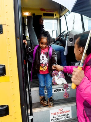 Preschooler Carin Bright, 4, steps down off the bus after arriving home following a day spent at the Dixon Education Center. Carin is greeted by her mother, Regina Bright, at the bus stop near where they live in Staunton on Tuesday, Oct. 27, 2015.