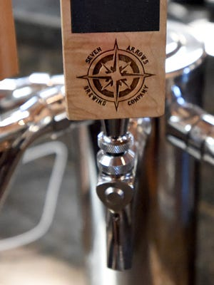 The Seven Arrows Brewing Company logo is on one of their beer taps behind the bar in Waynesboro.