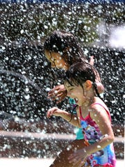Addison Adams-Payan, right, and Leila Owen scream as water from a large bucket splashes down on them during a sneak peek of the city's first spray park at Sue Young Park in Northeast El Paso in 2016.