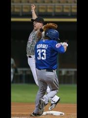 El Paso first baseman Patrick Kivlehan leaps to snag an errant throw as Las Vegas' Darin Gorski reaches first base Monday at Southwest University Park. All the runners were safe.