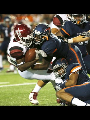 UTEP's Alvin Jones, top, and a teammate make a tackle against NMSU earlier this season.