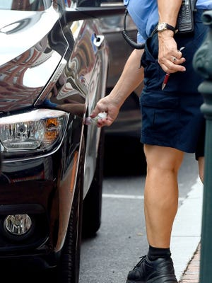 "Parking enforcement officer Mary Fitzgerald chalks the tires of vehicles parked along West Beverley Street. She goes about her job with the Staunton Police Department  on Thursday, Sept. 15, 2016. ""I've been at this for 21 years,"" she says about her time in parking enforcement."