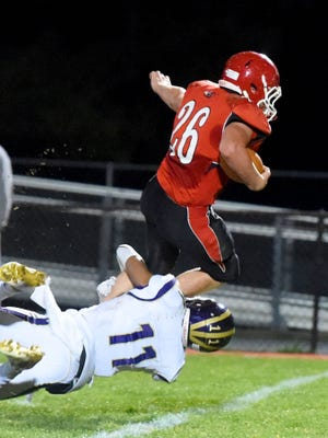 Riverheads' Dalton Jordan tries to leap over Essex's Isaiah Taylor who wraps him up around the legs and brings him down during a Region 1A East semi-final football game played in Greenville on Friday, Nov. 18, 2016.
