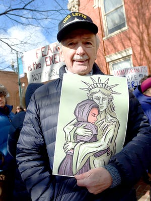 Navy veteran Russell Armentrout, age 87, of Staunton holds a drawing of the Statue of Liberty protecting a refugee. Armentrout is one of about 150 people attended an immigration policy protest held in front of the Augusta County Courthouse in downtown Staunton on Monday, Jan. 30, 2017.