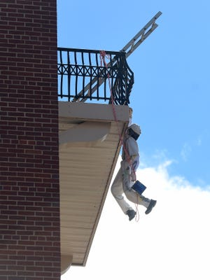 A creation of artist Mark Cline, the figure of a painter hangs off a balcony of the Robert E. Lee Hotel in Lexington for his annual prank on Saturday, April 1, 2017. The creation will remain in place for people to see and enjoy at least through Easter weekend, possibly longer.