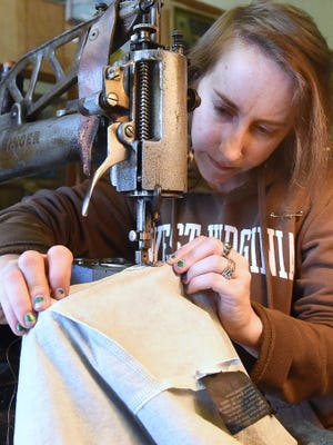 Yvonne Young uses a vintage leather sewing machine to stitch a tear in a raincoat being repaired for an Appalachian Trail thru-hiker at Graham's Shoe Repair on May 11, 2017.