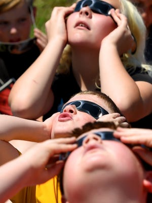 Fifth-graders use protective glasses as they watch the solar eclipse outside Riverheads Elementary on Monday, Aug. 21, 2017.
