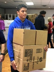 Lee High's Jayden Williams carries boxes full of items that will be distributed by the Staunton Elks Lodge to families in need this Christmas season.