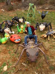 """Artist Mark Cline """"rides"""" a larger-than-life ant he created that will be used in his annual April Fool's Day creation."""