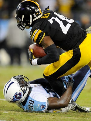 Steelers running back Le'Veon Bell (26) powers over Titans cornerback Jason McCourty in the fourth quarter Monday.