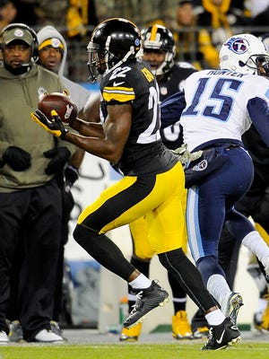 The Steelers' William Gay (22) intercepts a pass intended for Titans wide receiver Justin Hunter and returns if for a touchdown in the first quarter Monday.
