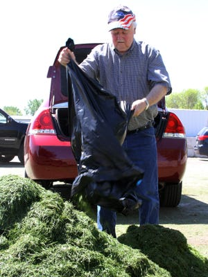 Ron Voskuil empties a leaf bag of grass clippings at the city yard debris collection site at the central garage in this 2014 file photo.