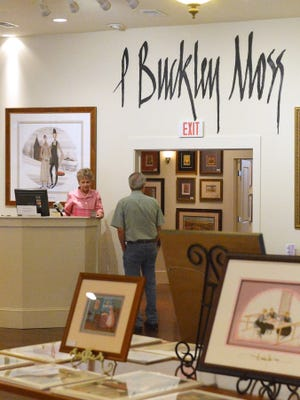 Jo Cowherd of P. Buckley Moss Waynesboro Gallery assists a visitor Wednesday.